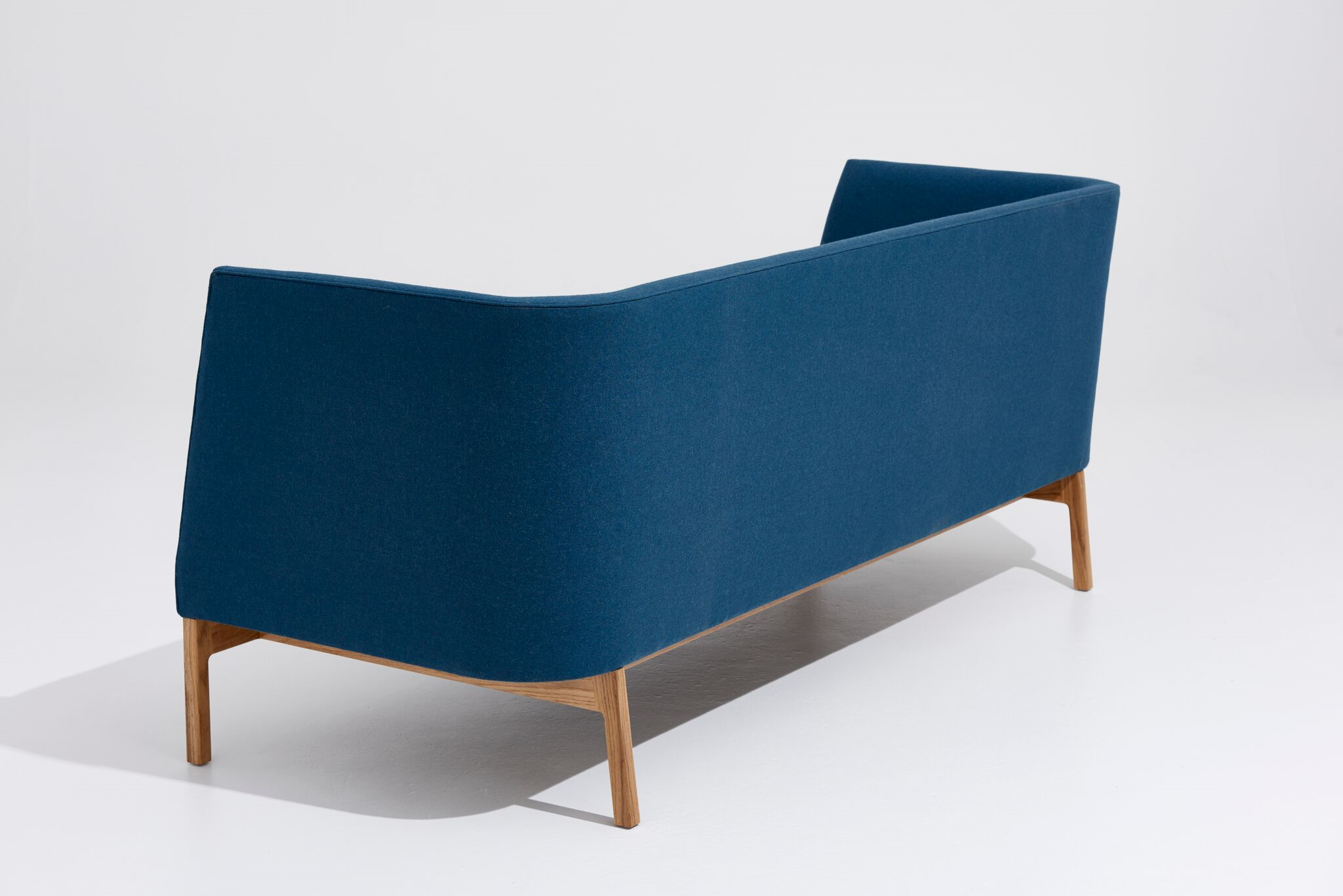 The back of the sofa is comprised of a visually appealing curved form.